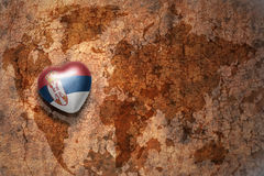 Heart with national flag of serbia on a vintage world map crack paper background. Concept Stock Images