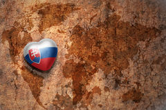 Heart with national flag of slovakia on a vintage world map crack paper background. Concept Royalty Free Stock Image