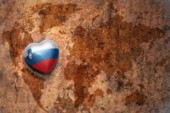 Heart with national flag of slovenia on a vintage world map crack paper background. Concept Stock Photos