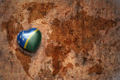 Heart with national flag of Solomon Islands on a vintage world map crack paper background. Concept Stock Photo