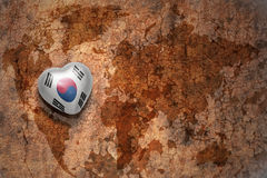 Heart with national flag of south korea on a vintage world map crack paper background. Concept stock photography