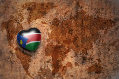 Heart with national flag of south sudan on a vintage world map crack paper background. Stock Photography