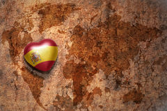 Heart with national flag of spain on a vintage world map crack paper background. Concept Stock Photos