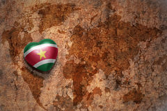 Heart with national flag of suriname on a vintage world map crack paper background. Stock Images