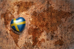 Heart with national flag of sweden on a vintage world map crack paper background. Concept Royalty Free Stock Photo