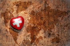 Heart with national flag of switzerland on a vintage world map crack paper background. Concept Royalty Free Stock Photo