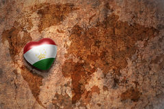 Heart with national flag of tajikistan on a vintage world map crack paper background. Concept Royalty Free Stock Images