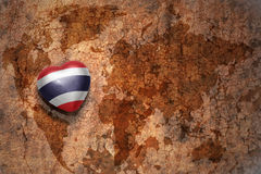 Heart with national flag of thailand on a vintage world map crack paper background. royalty free stock images
