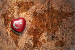 Heart with national flag of turkey on a vintage world map crack paper background. Concept Royalty Free Stock Photography