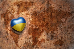 Heart with national flag of ukraine on a vintage world map crack paper background. Concept Royalty Free Stock Images
