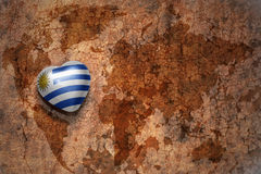 Heart with national flag of uruguay on a vintage world map crack paper background. Concept Royalty Free Stock Photos