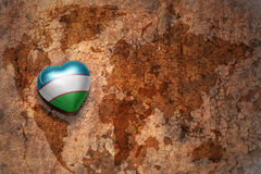 Heart with national flag of uzbekistan on a vintage world map crack paper background. Concept Stock Photo