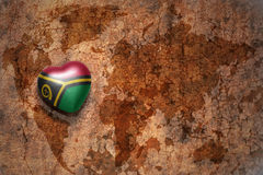 Heart with national flag of Vanuatu on a vintage world map crack paper background. Concept Stock Photography