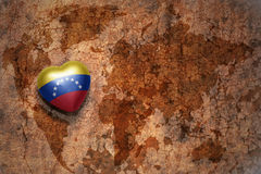 Heart with national flag of venezuela on a vintage world map crack paper background. stock photo