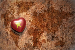 Heart with national flag of vietnam on a vintage world map crack paper background. Concept royalty free stock image