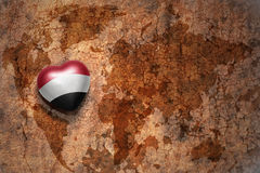 Heart with national flag of yemen on a vintage world map crack paper background. Concept Stock Photo