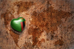 Heart with national flag of zambia on a vintage world map crack paper background. stock image