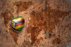 Heart with national flag of zimbabwe on a vintage world map crack paper background. Royalty Free Stock Photo
