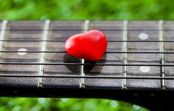 Heart on neck guitars and strings on the grass Stock Photography