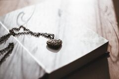 A heart necklace on an open book Royalty Free Stock Photography