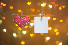 Heart and needles with blank photo on clothesline. Valentines day concept. Heart and needles with note on clothesline. Valentines day concept. Over heart bokeh Royalty Free Stock Image