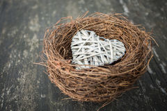 Heart in nest on wooden background in country style. Royalty Free Stock Image