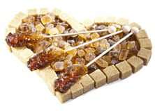 Heart from not refined reed sugar and candy sugar on a stick Royalty Free Stock Photo