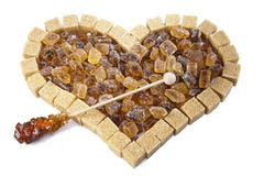 Heart from not refined reed sugar and candy sugar on a stick Royalty Free Stock Images