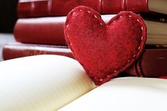 Heart love card with notebook. Red heart made of felt put on a blank page notebook in a library for valentine`s day. A present for the Valentine`s Day royalty free stock photo
