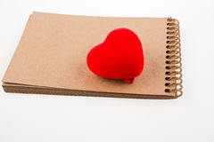 Heart on notebook. Red heart shape on the spiral notebook Stock Images