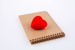 Heart on notebook. Red heart shape on the spiral notebook Stock Photo