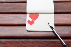 Heart with a notebook on a table Stock Photography