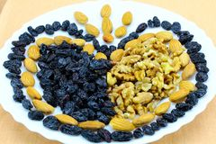 Heart of nuts and raisins in white dishes stock image