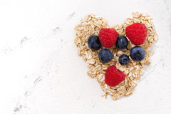 Heart of oat flakes and fresh berries Royalty Free Stock Photo