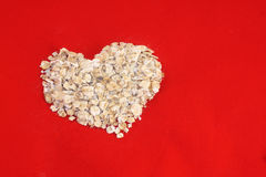 Heart Oats. Dry rolled oats in a heart shape on a red background Royalty Free Stock Images