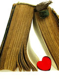 Heart and old closed the book with a damaged cover. Royalty Free Stock Photo