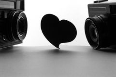 Heart and old retro cameras. Space for text or image. Love photography concept. Royalty Free Stock Image