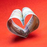 Heart from one hundred dollar bills USA. Red background. Square frame for instagram. Concept of money and love and a gift for royalty free stock photography