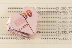 Heart origami folding Baht bank note on opening saving account passbook Stock Photo