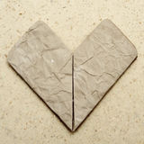 Heart. An origami heart made with a wrinkled old paper on a granite background with a retro effect Royalty Free Stock Photography
