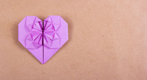 Heart of origami of purple paper on brown recycled paper. Royalty Free Stock Photos