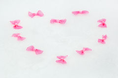 Heart of ornamental bows on white snow Stock Image