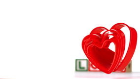 Heart ornaments falling with blocks spelling love in background stock video footage