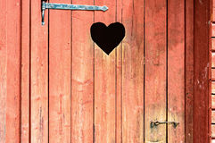 Heart. Outdoor toilet door with carved heart below iron hinge. Old traditional marking for outhouses in Scandinavia. Heart also serve as window or inspection Royalty Free Stock Image