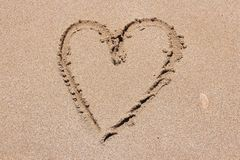 Heart outline. Finger drawing on a sandy beach - heart shape, symbol of love royalty free stock photo