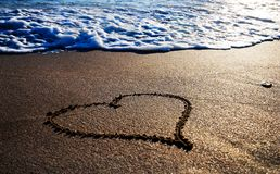 Heart outline on the wet sand. With the wave brilliance Royalty Free Stock Photo