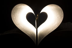 Heart in pages. The pages of a bible forming a heart dramatically lit from behind Stock Image