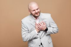 Heart pain attack. Profile side view portrait of middle aged bal. D bearded businessman in light gray suit standing and holding his rib cage. indoor studio shot royalty free stock photo
