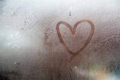A heart painted on a misted window. Heart on misted glass. Heart on a window background.Heart symbol of love drawn on the glass royalty free stock photography
