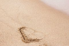 The heart painted on the sand is partially washed away by the wave stock photography